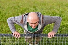Man doing pushups outdoors on a bench, Closeup Stock Photography