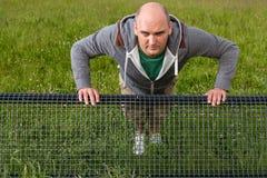 Man doing pushups outdoors on a bench, Closeup Stock Image