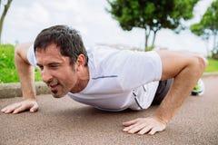 Man doing pushups outdoors. Mid adult man doing pushups outdoors Stock Photos