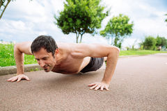 Man doing pushups outdoors. Mid adult man doing pushups outdoors shirtless Stock Image