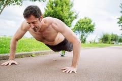 Man doing pushups outdoors Stock Images