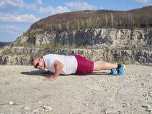 Man doing pushups outdoors in nature. Stock Photos