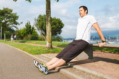 Man doing pushups outdoors using a bench. Mid adult man doing pushups outdoors using a bench Stock Photography