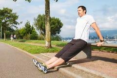 Man doing pushups outdoors using a bench Stock Photography