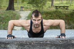 Man doing pushups on wooden log. Royalty Free Stock Photos