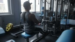Man is doing seated row. In gym stock video