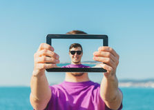 Man doing a self-portrait with him digital tablet on beach Royalty Free Stock Photos