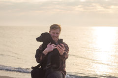 Man doing selfie with dog. Young caucasian male walking with dog on the morning beach, sunset on the sea or ocean and man with black labrador puppy Stock Image