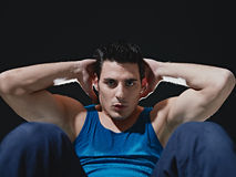 Man doing series of sit-ups on black background Royalty Free Stock Photos