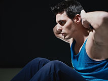 Man doing series of sit-ups on black background Stock Images
