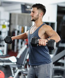 Man doing shoulder workout in a gym Stock Images