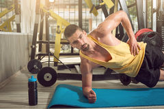 Man doing side plank exercise in gym stock photos