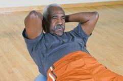 Man Doing Sit-Ups. Senior man doing sit-ups on a pilates ball Stock Image