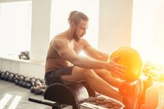 Man doing sit ups with medicine ball on bench, working on abdominal muscles. E view of fit young man doing pilates, working on abdominal muscles. Fitness man Royalty Free Stock Photography