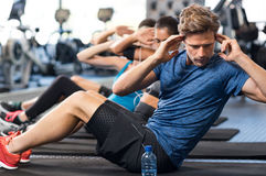 Man doing sit ups. Muscular guy doing sit ups at gym with other people in background. Young athlete doing stomach workout in modern gym. Handsome fit men doing Royalty Free Stock Image
