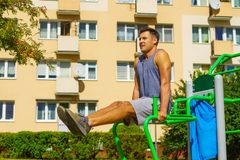 Man doing sit ups in outdoor gym. Young handsome man working out in outdoor gym. Sporty guy flexing his muscles doing sit ups on machine in park. Staying fit and royalty free stock photos