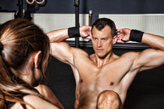 Man doing situp crunches with support Royalty Free Stock Photo