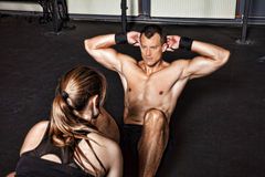 Man doing situp crunches with support. In a gym Stock Image