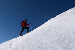 Ski touring. Man doing ski touring and ascending the hill Stock Images
