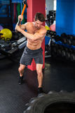 Man doing sledgehammer swing exercise. Young shirtless man doing sledgehammer swing exercise in gym Royalty Free Stock Photo