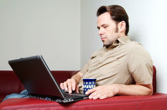 Man doing some laptop worh at home Stock Images