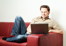 Man doing some laptop worh at home Stock Photos