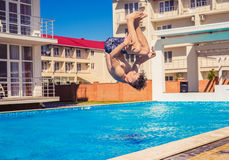Man doing Somersaul or flip diving into swimming pool. Party at smimming pool. Man doing Somersaul or flip diving into swimming pool . Happy youth time Stock Photo