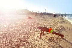 A man is doing sports on the beach. Crossfit training fitness man plank exercise Stock Images