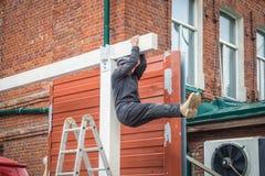Man doing a sports exercise on a press. A strong construction man in dark construction overalls doing a sports exercise on a press and hanging on a wooden stock photos