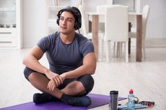 The man doing sports at home and listening to music. Man doing sports at home and listening to music Royalty Free Stock Photo