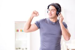 The man doing sports at home and listening to music. Man doing sports at home and listening to music Stock Photo