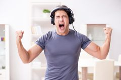 The man doing sports at home and listening to music. Man doing sports at home and listening to music Stock Image