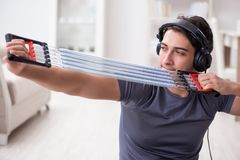 The man doing sports with resistance band and listening to music. Man doing sports with resistance band and listening to music Royalty Free Stock Image