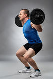 Man doing squats with barbell Stock Image