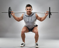 Man doing squats with barbell Royalty Free Stock Images
