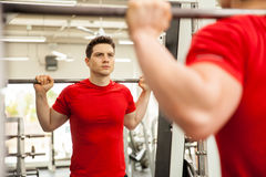 Man doing squats on a smith machine Royalty Free Stock Image