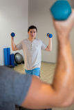 Man doing step aerobic exercise with dumbbell on stepper. In fitness studio Stock Photos