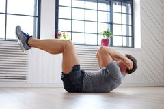 A man doing stomach workouts. Athletic middle age man doing stomach workouts at home Stock Images