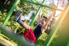Man doing stomach workouts on horizontal bar outdoors Stock Photo