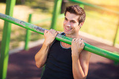 Man doing stomach workouts on horizontal bar outdoors Royalty Free Stock Photography