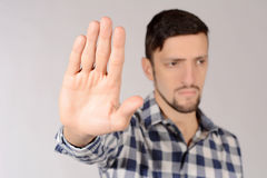 Man doing stop gesture. Young man doing stop gesture with hand. Isolated white background Royalty Free Stock Image