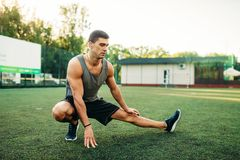 Man doing stretching exercise on outdoor workout. Man in sportswear doing stretching exercise on outdoor fitness workout. Strong sportsman on training in park Stock Photos