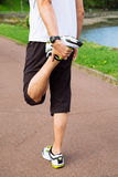 Man doing stretching exercises outdoors. Legs of sportsman doing stretching exercises outdoors in a track before running Royalty Free Stock Photo