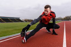 Man doing stretching in the outdoor running track Royalty Free Stock Images