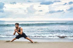 Man Doing Stretching Workout Exercises, Exercising At Beach. Fitness Royalty Free Stock Photo