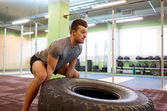 Man doing strongman tire flip training in gym Stock Photo