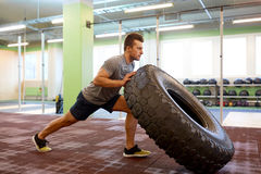 Man doing strongman tire flip training in gym Stock Images