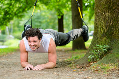 Man doing suspension trainer sling sport Stock Photos