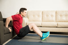 Man doing tricep dips using a couch at home Stock Images