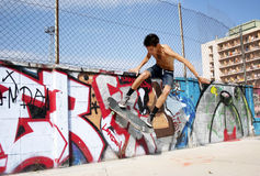 Man Doing Tricks on Skateboard Near Graffiti Wall Royalty Free Stock Photography